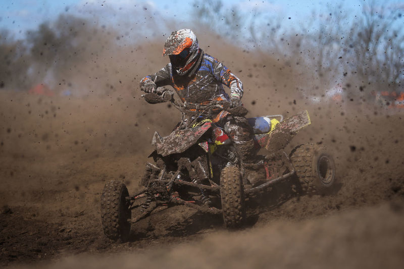 Racer Riding Quadbike In Dirt During Race