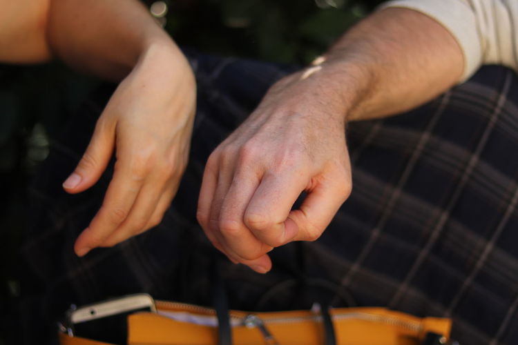 Cropped Hands Of Couple On Bag