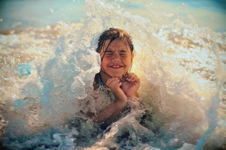 Wave splashing on girl in sea