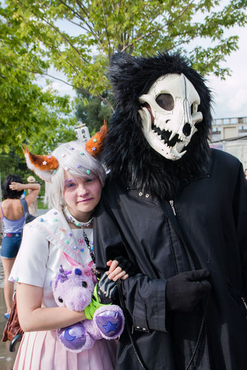 Cosplay Celebration Costume Disguise Dressing Up Females Halloween Leisure Activity Lifestyles Looking At Camera Make-up Mask Mask - Disguise Men Outdoors People Real People Standing Togetherness Two People Waist Up Women