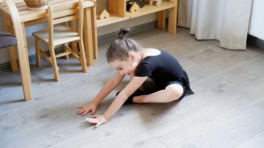 High angle view of girl sitting on hardwood floor at home