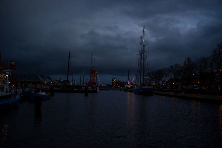 Sailboats in sea against sky at dusk