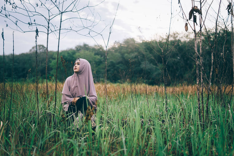 Woman Wearing Hijab Sitting On Grassy Field