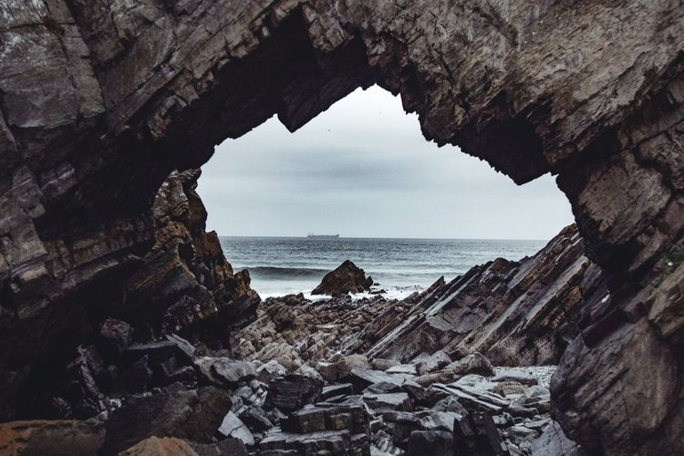Scenic View Of Sea Seen Through Arch Shaped Rock Formation