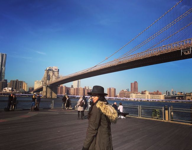Young woman standing at promenade by brooklyn bridge over east river