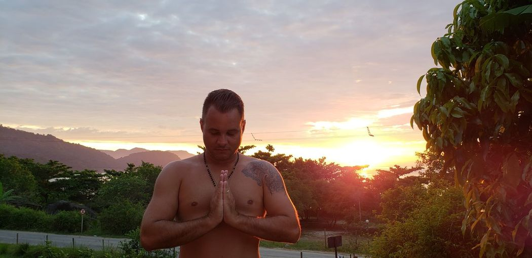Shirtless man with hands clasped standing against cloudy sky during sunset