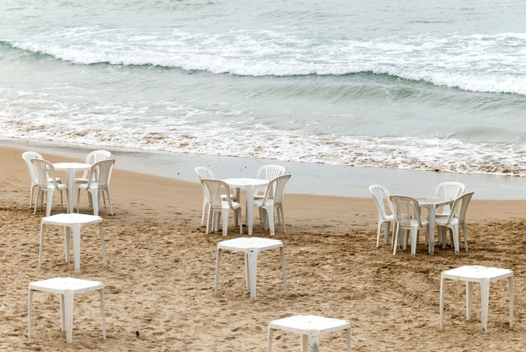 Beach with tables and chairs in the morning Armação De Búzios Brazil Rio De Janeiro Absence Aquatic Sport Beach Beauty In Nature Chair Day Land Motion Nature No People Outdoors Sand Sea Seat Sport Tranquil Scene Tranquility Water Wave White Color