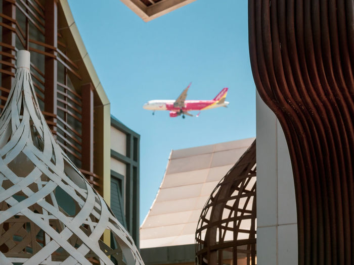 Low angle view of airplane flying in building against sky