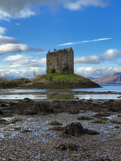 Castle by sea against sky