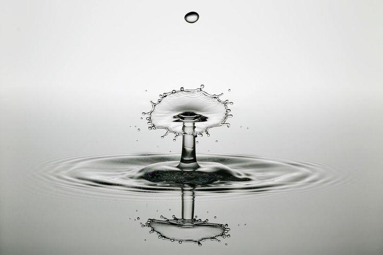 Close-up of water splashing on white surface
