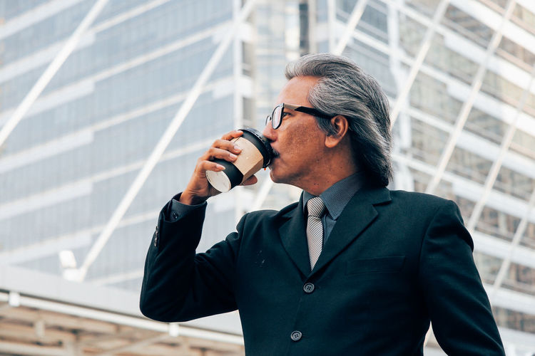 Businessman drinking coffee against office building