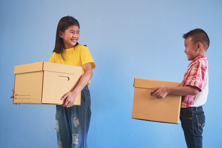 Smiling boy and girl holding shopping bags and container against colored background