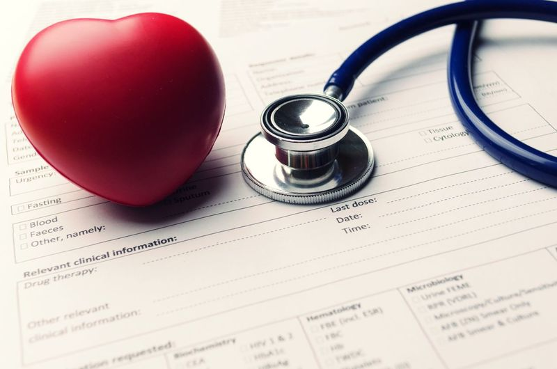Close-up of heart and stethoscope on papers