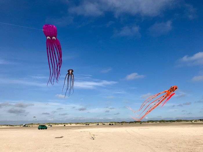 Scenic view of beach umbrellas against blue sky