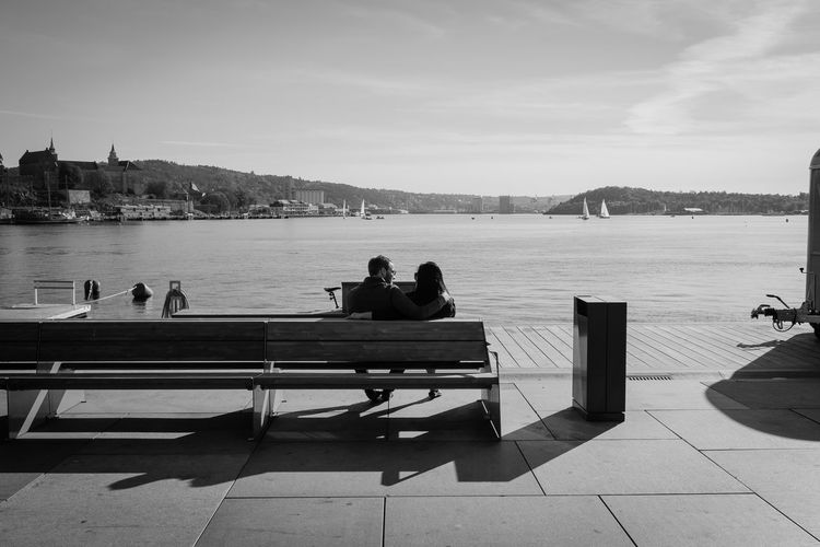 Rear View Of Couple Sitting On Bench At Harbor Against Sky