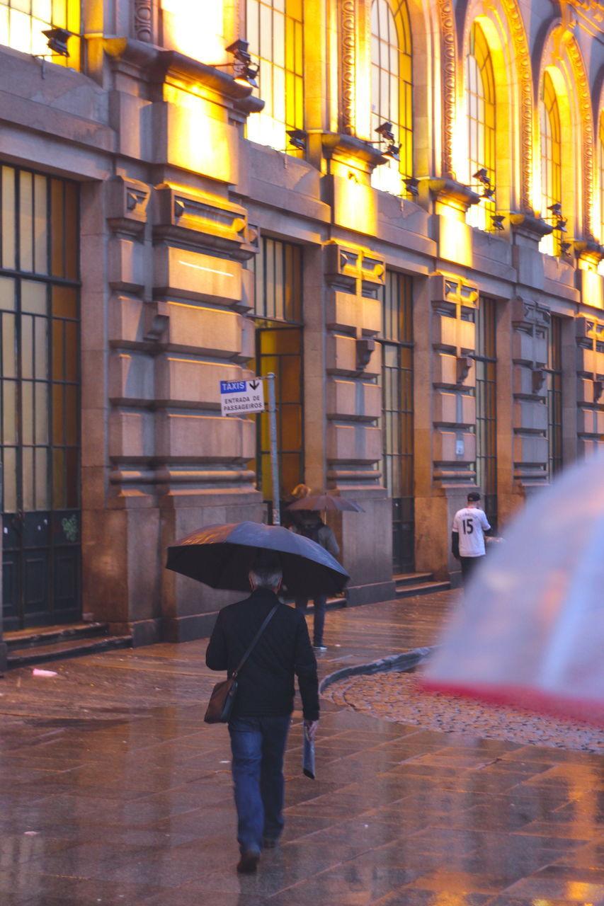 REAR VIEW OF WOMAN WALKING ON ROAD ALONG BUILDINGS