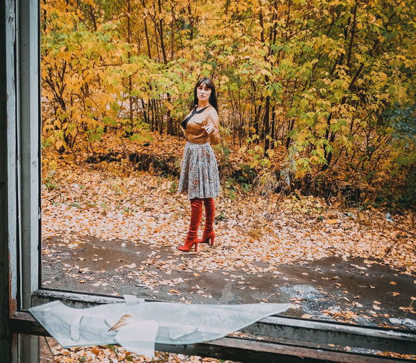 Full Length Portrait Of Woman Against Autumn Trees On Field Seen Through Broken Glass Window