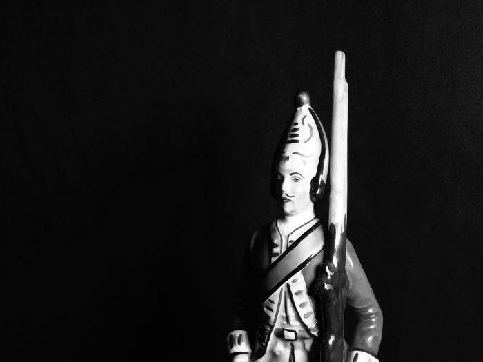 Porcelin soldier against black background