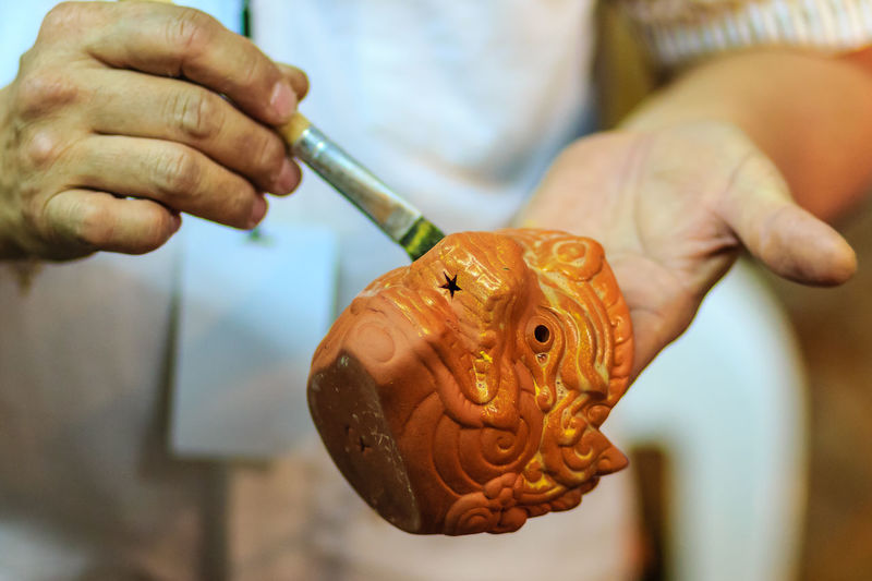 Close up hand of Thai sculptor during painting the masterpiece of hanuman puppet doll at night market Ceramic Ceramic Art Ceramic Art Craft Clay Clay Art Clay Dolls Clay Work Hanuman Masterpiece Painting Puppet Puppet Doll Sculptor