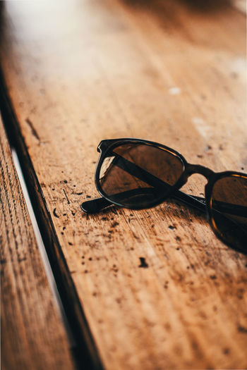 Brown Close-up Day Eyeglasses  Eyewear Fashion Glass - Material Glasses High Angle View Indoors  No People Personal Accessory Protection Security Selective Focus Still Life Sunglasses Table Transparent Wood - Material