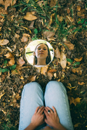 Reflection Of Young Woman On Mirror At Field