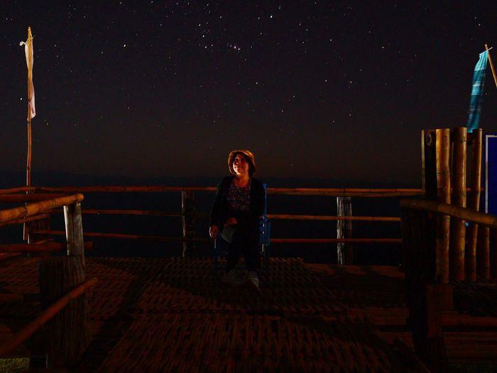 Full length of woman sitting on railing at night