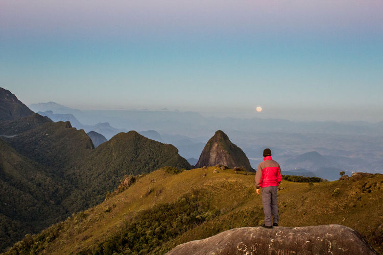 Man on a rock on the mountains looking at moon rising in Morro da Ventania, Brazil. On The Mountain Moon Moon Over The Mountains One Person Outdoors Non-urban Scene Sky Scenics - Nature Looking At View Branch Hikingadventures