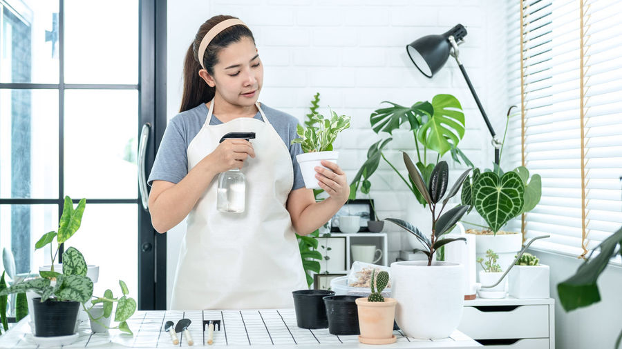 Young woman using phone while standing on potted plant