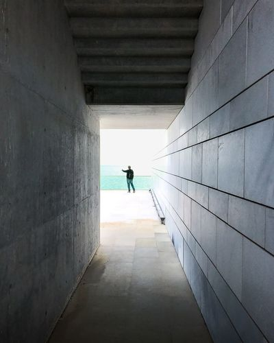 Rear View Of Man Standing By Sea Seen Through Tunnel