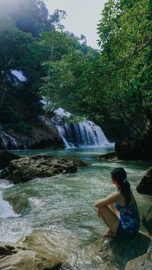 Man sitting on rock against waterfall