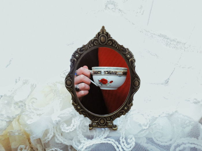 Reflection of woman holding cup in mirror