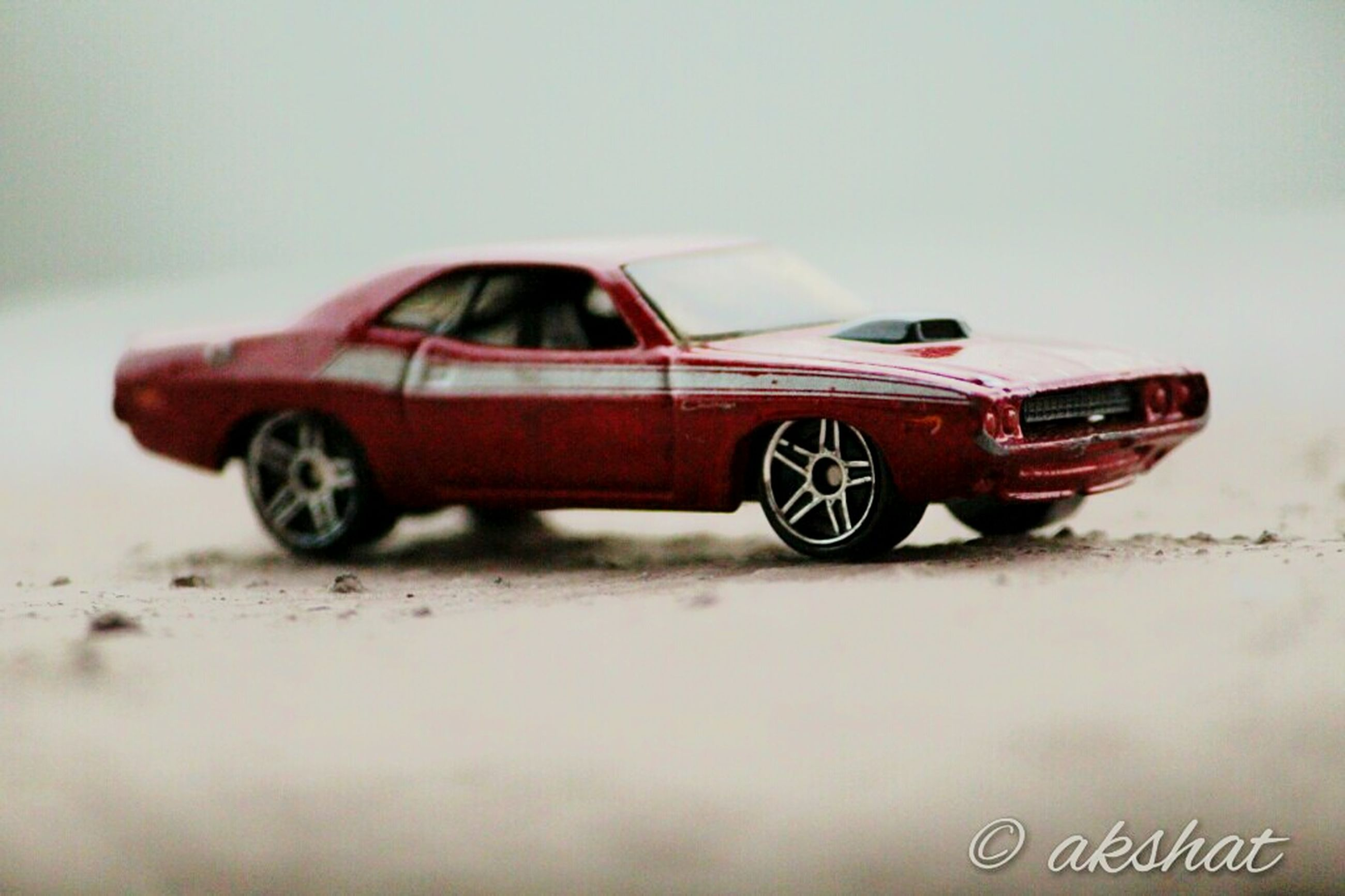 transportation, close-up, land vehicle, car, mode of transport, selective focus, red, copy space, focus on foreground, no people, single object, day, outdoors, abandoned, still life, old, toy, part of, obsolete, road