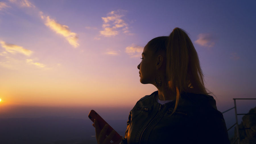 Young woman holding mobile phone while standing against sky during sunset