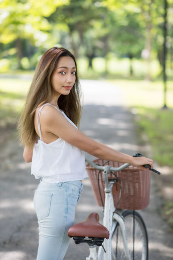 Portrait of beautiful woman standing by bicycle