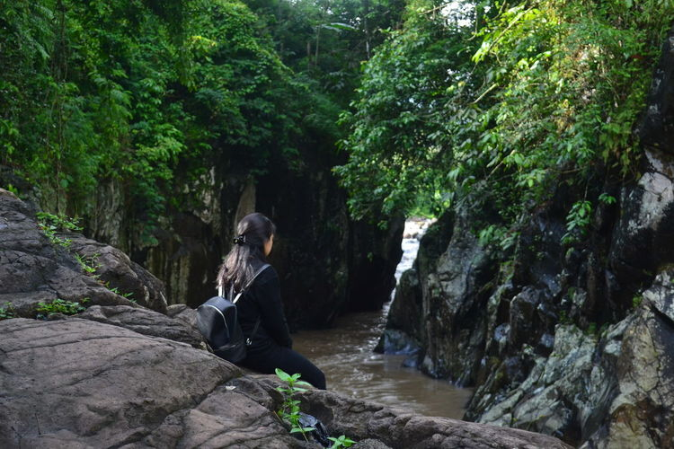 Woman sitting on rock by river