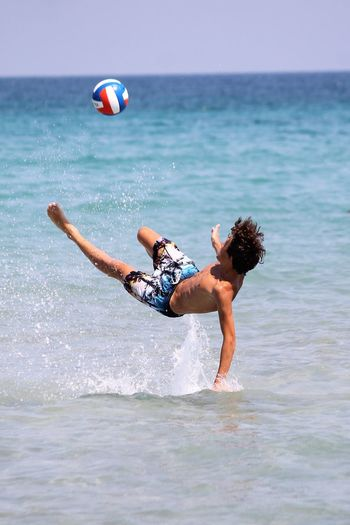 Man playing in sea football passion