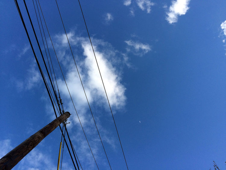 a deep blue sky whose clouds float above the electric human condition. Blue Cable Cloud Complexity Connection Day Electric Pole Electricity  Float Low Angle View Nature Outdoors Pole Power Power Line  Power Supply Sky Technology Up White
