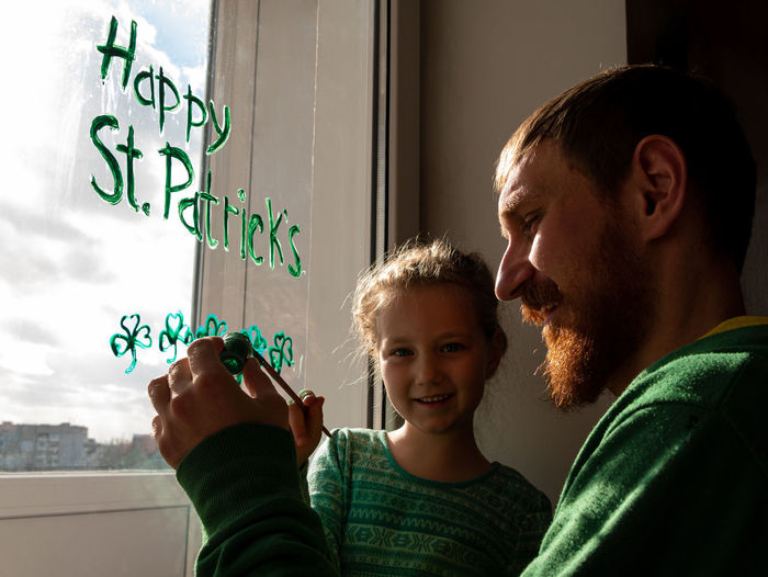Drawing st. patrick's day father daughter painting green three-leaved shamrocks.stay home new normal