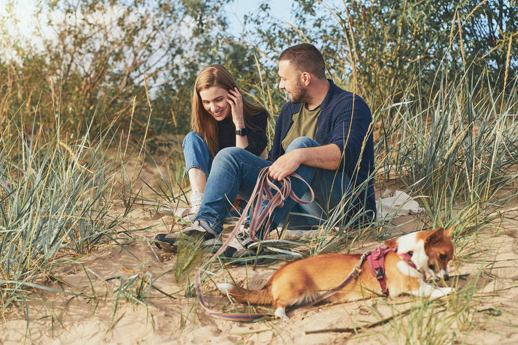 Young happy couple of man and woman with corgi dog sit at sand. two persons in casual clothes