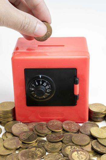 Hand holding coins and put into red safe box Human Hand Finance Coin Hand Wealth Human Body Part Currency Savings Finger Human Finger Business One Person Investment Body Part Holding Red Real People Technology Close-up Indoors