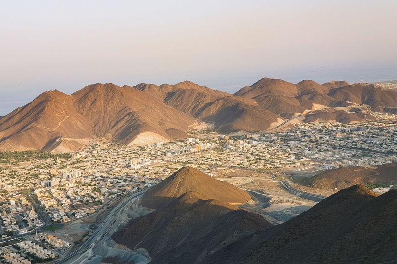 Scenic view of desert mountains against sky in khorfakan uae.