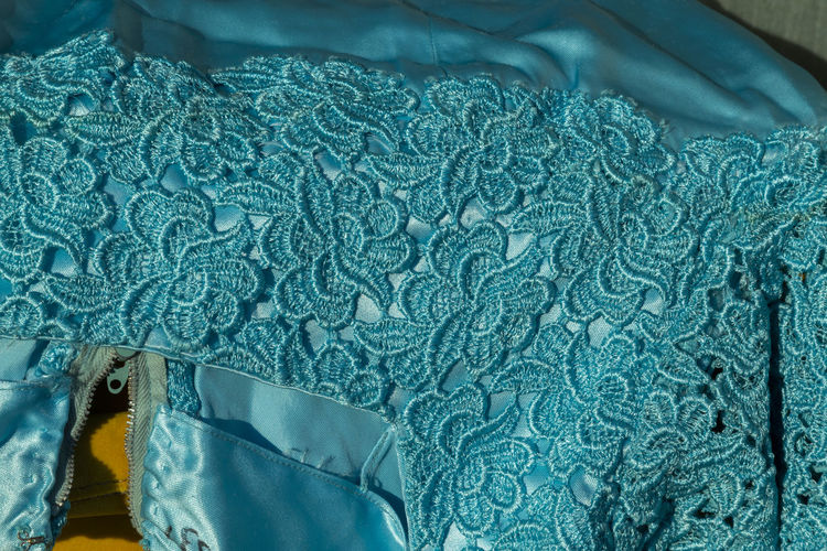 Close up of suare neckline of a cocktail dress in turquoise satin and macrame lace