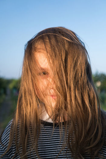 Portrait Of Girl With Messy Hair Against Blue Sky