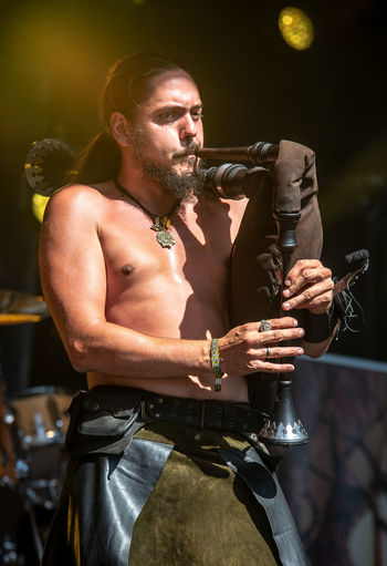 Low Angle View Of Shirtless Man Playing Bagpipe During Concert