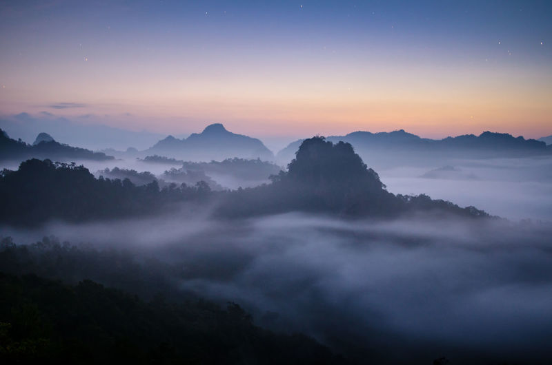 Scenic view of silhouette mountains in foggy weather during sunrise