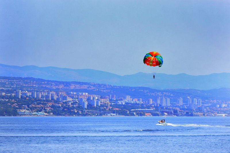 View of hot air balloon flying over sea against sky