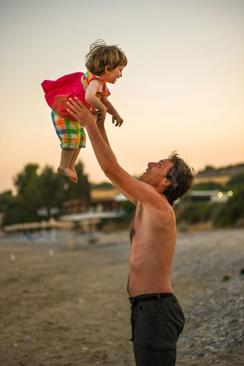 Shirtless father carrying daughter while standing at beach against sky
