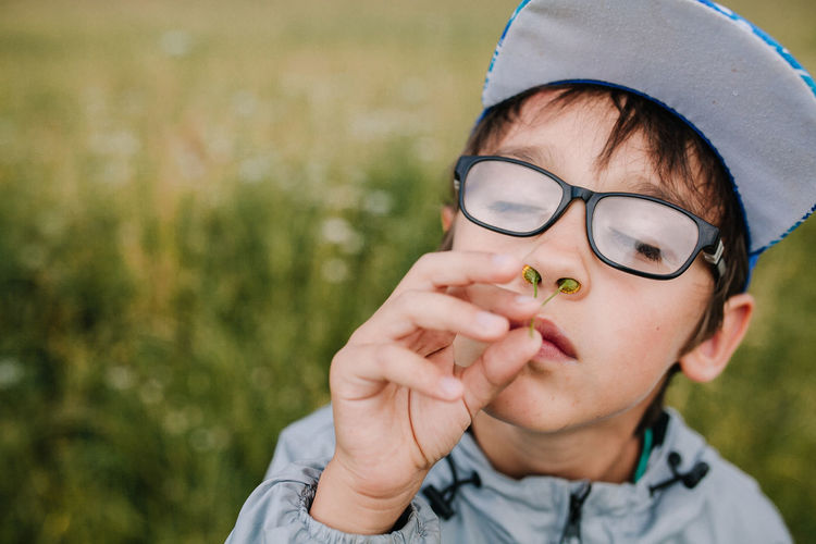 Close-up of boy putting flower into nose outdoors