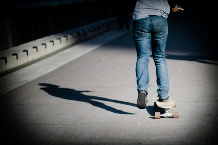 Rear view low section of skateboarding on road