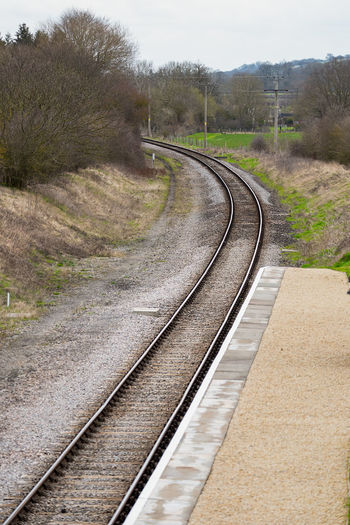 A empty railway track on a sweeping picture away from an empty basic station platform. Broadway Stattion Gloucestershire Gloucestershire Warwickshire Railway Broadway Cotswolds Easter Weekend  Glous Granding Opening Heritage Railway New Line News Passenger Train Track Railroad Track Direction The Way Forward Rail Transportation Transportation No People Tree Plant Curve Nature Day Road Diminishing Perspective Mode Of Transportation Public Transportation Outdoors Sky Growth Absence Long Parallel